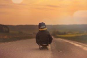 Enfant de dos skateboard sur une route
