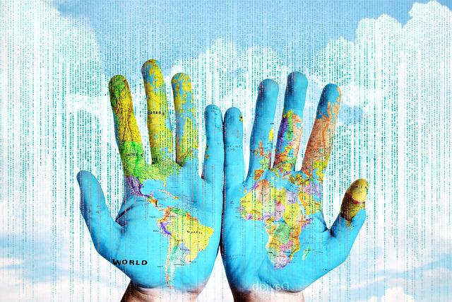 Carte du monde projetée sur deux mains, sur fond de nuage avec pluie de chiffres